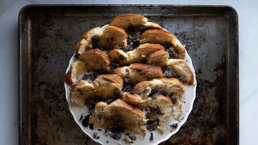 Slices of brioche in a tart dish covered in marmalade and custard mixture, sprinkled with sultanas and chocolate, winter dessert