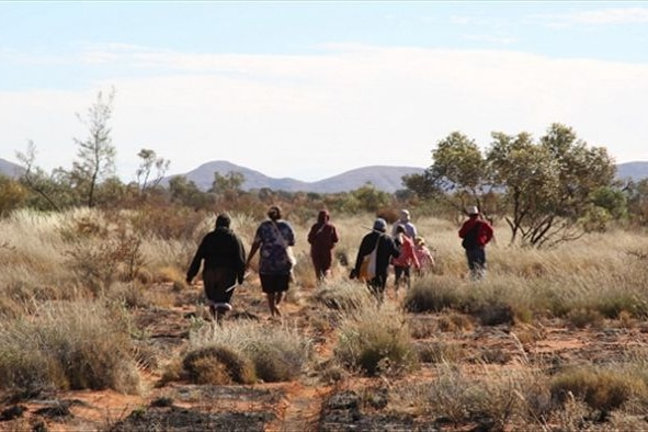 A group of people walking through a sparse landscape.