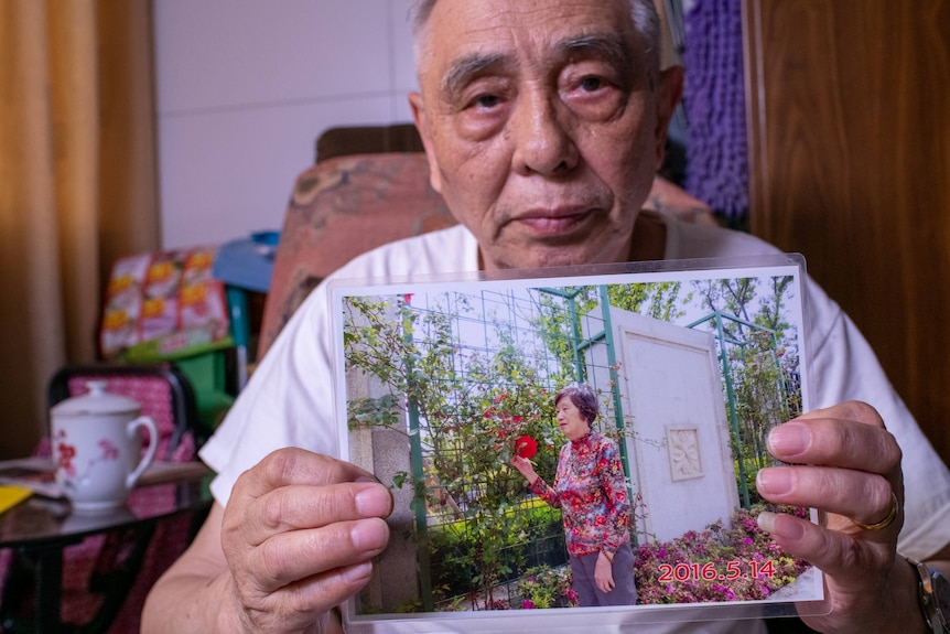 An old Chinese man holds up a picture of a middle-aged woman in a garden.