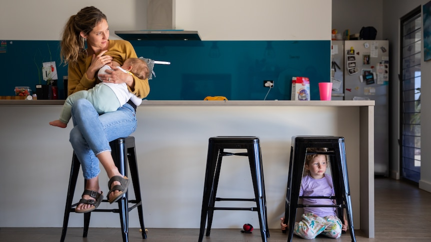 Kara breast feeds her youngest, Lachy, in the kitchen.