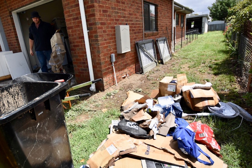 Matthew Willey of Euroa cleans out some of the flood-damaged possessions from his house.