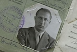 Black and white passport documents of a man in his thirties with tanned skin, piercing eyes, and sandy blond hair in a suit.