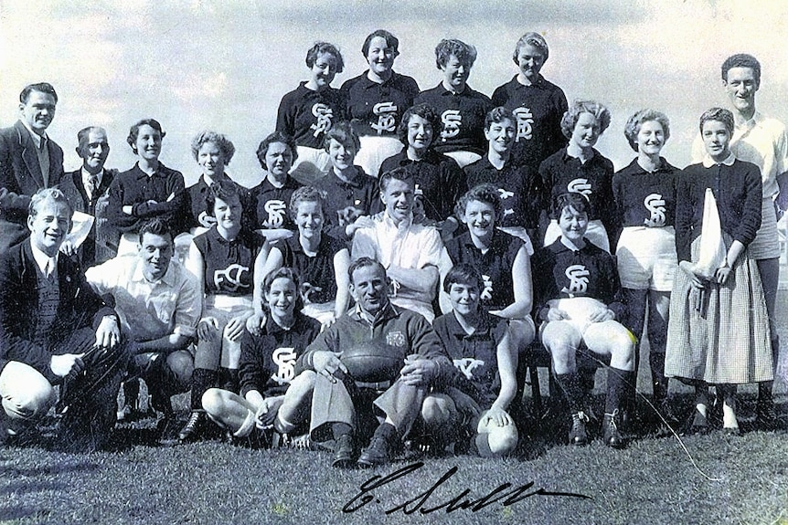 A group of young women in Carlton football jumpers sitting around a man holding a football.