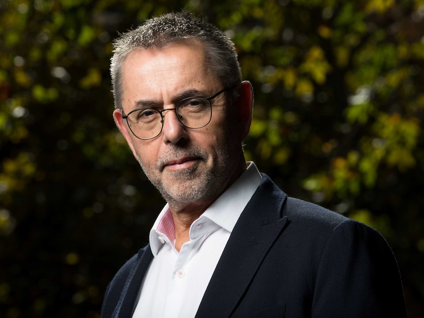 A man in glasses stares down the camera with a serious look on his face, he is surrounded by trees