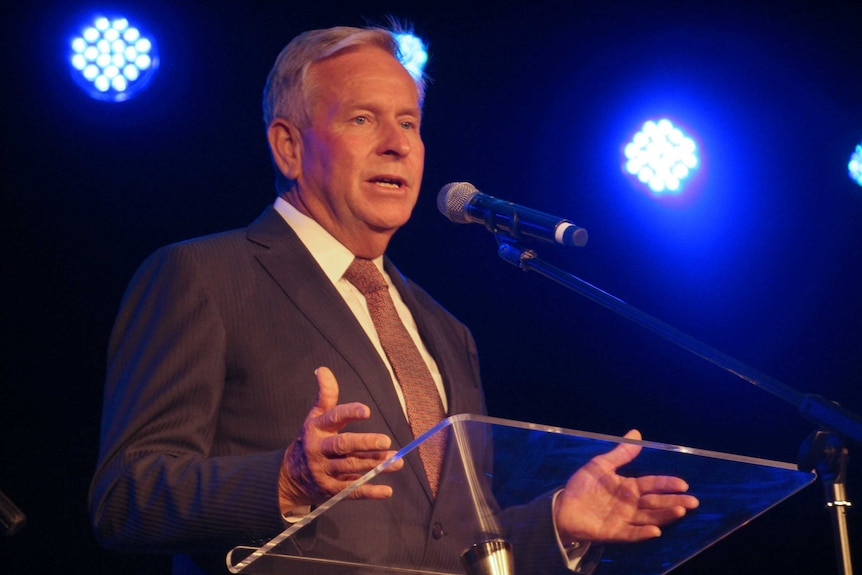A mid shot of Colin Barnett talking into a microphone at a pedestal.