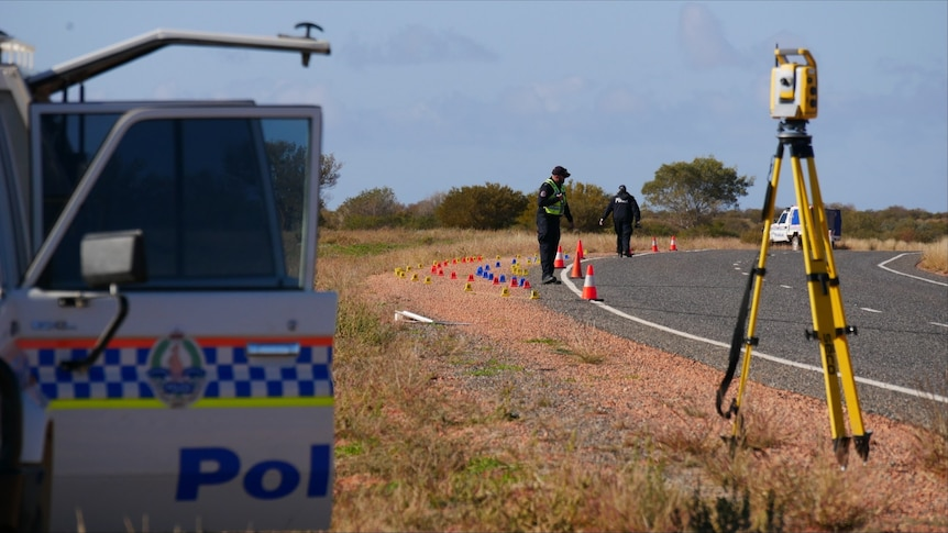 Police inspect the side of a highway in the Central Australian outback, near some road markers and a police vehicle.