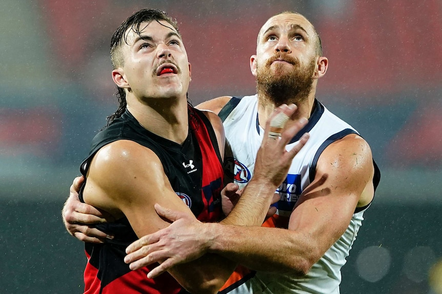 An Essendon AFL players and a GWS opponent push against each other as they prepare to contest for the ball.