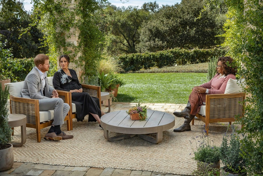 Prince Harry and Meghan sit on armchairs opposite Oprah Winfrey on a patio in a lush, green garden.