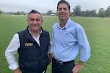 Dave Layzell and John Barilaro at a sports ground.