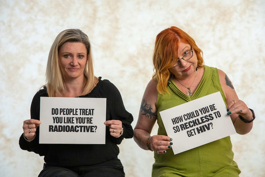 Natalie and Angela are holding cards with questions on them about HIV.