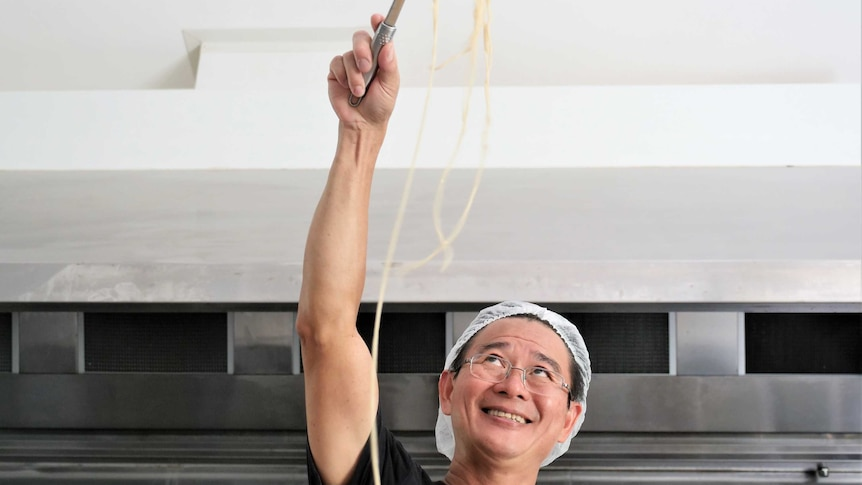 Shing Hee Ting cooking noodles in his kitchen