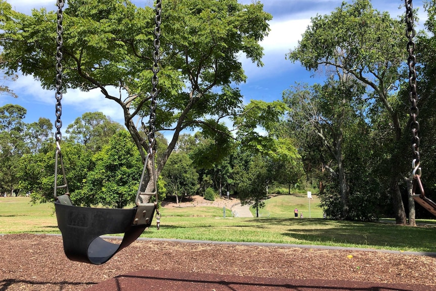 A children's swing in a park surrounded by trees.