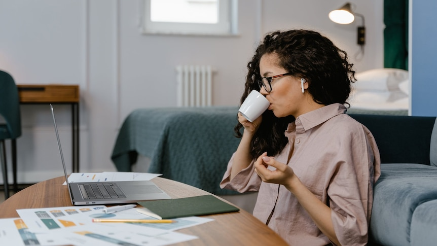 A woman sits at a coffee table, looking at her laptop, in story about tax time when working from home, have crypto investments.
