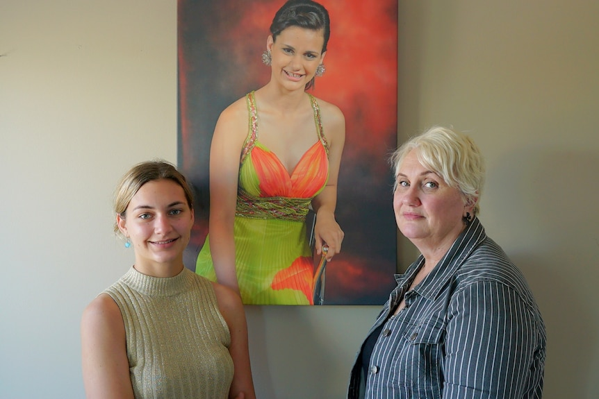 A teenage girl and her mother stand in front of a painted portrait of a young woman in a formal dress
