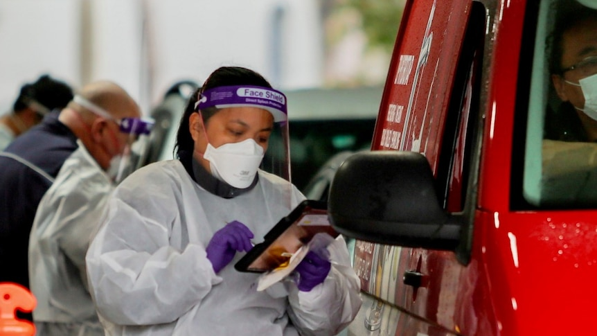 A healthcare worker in PPE near a driver in a red car at a testing site.