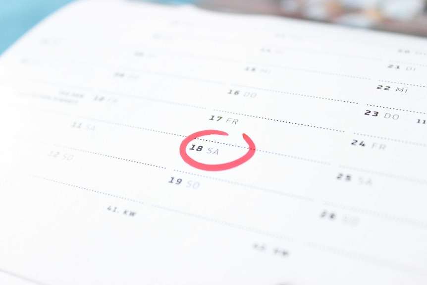 A calendar, with a date circled in red marker, to depict time management techniques.