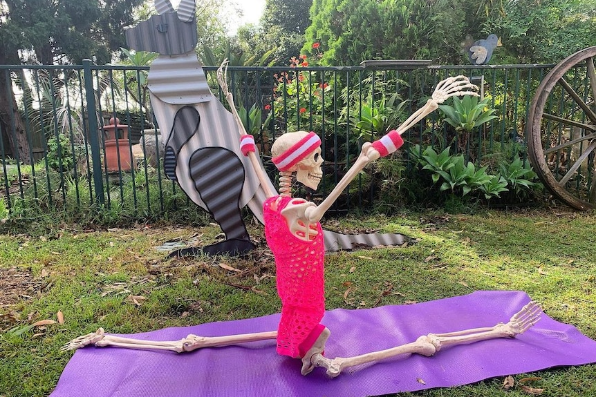 A skeleton doing the splits on a purple yoga mat on grass with its hands in the air.