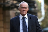 A mid-shot of John Poynton walking outdoors in the Perth CBD wearing a suit and tie.