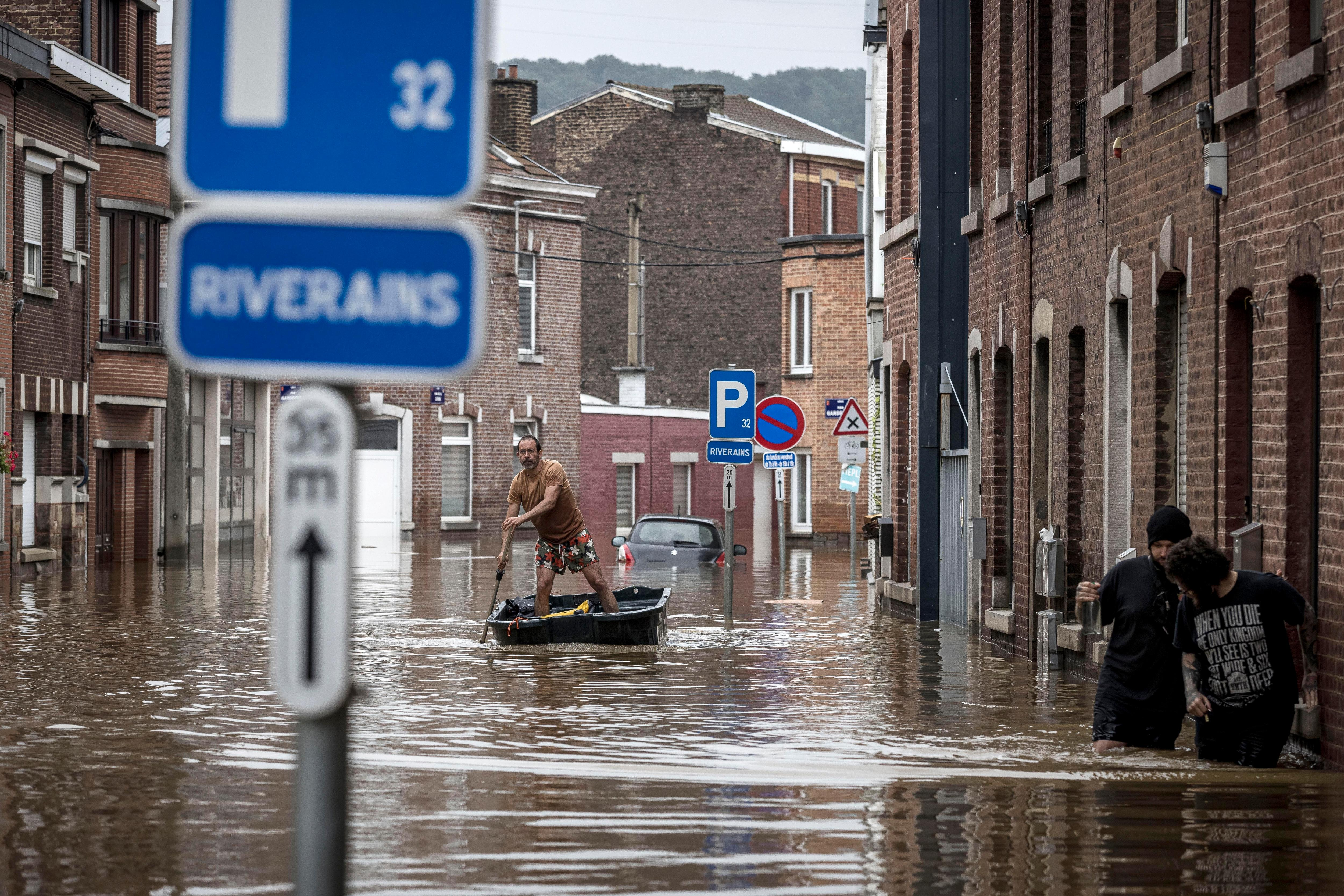 A man stands up rowing a small boat through a flooded street in Liege, Belgium.