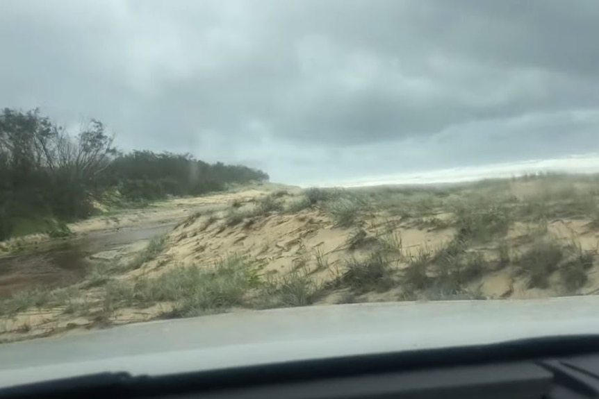 The video appears to show the vehicle stopped on a sand dune while the occupants inspect a creek crossing.