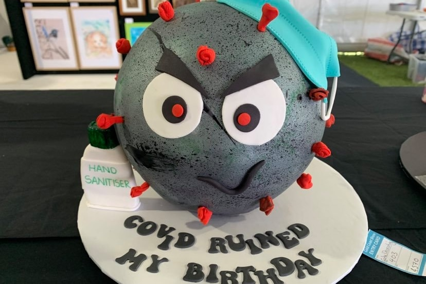 """cake ball looking like a germ, with the words """"COVID RUINED MY BIRTHDAY"""""""