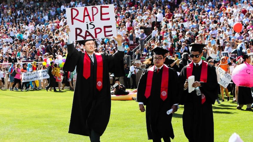 Graduate carries sign that reads: Rape is rape.