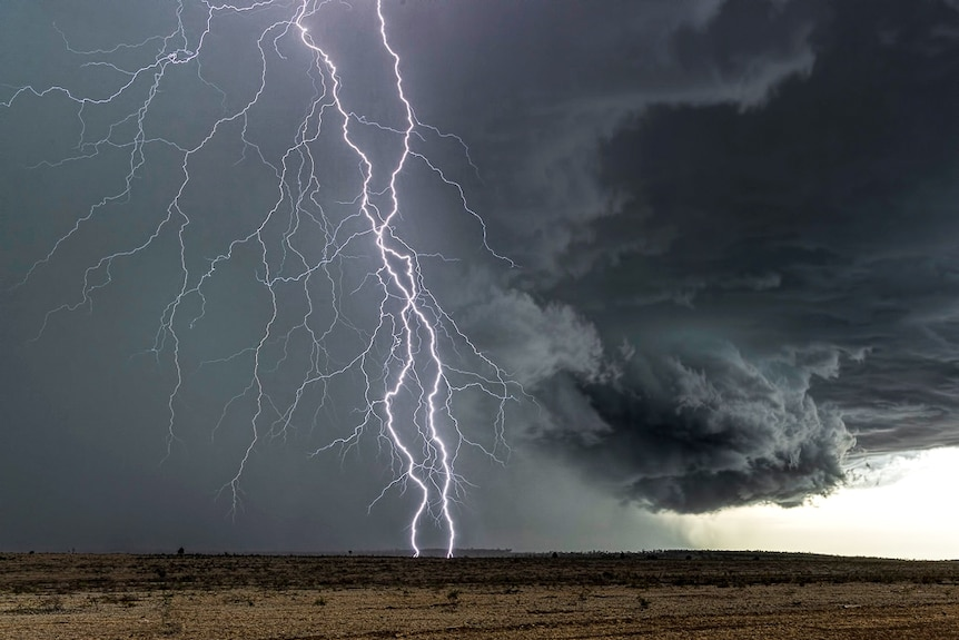 Lightning across the sky with a black cloudy background dry paddocks into the distance