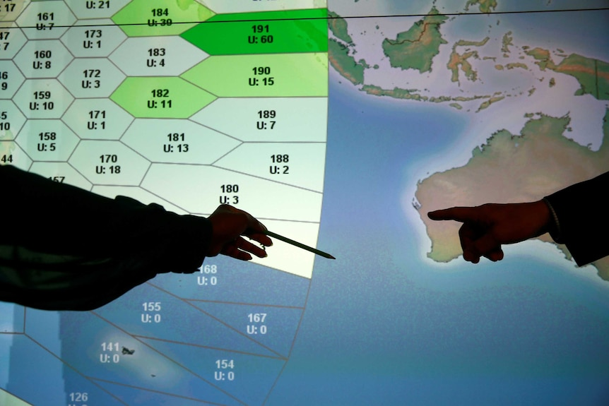 Member of staff at satellite communications company Inmarsat point to a MH370 search zone.