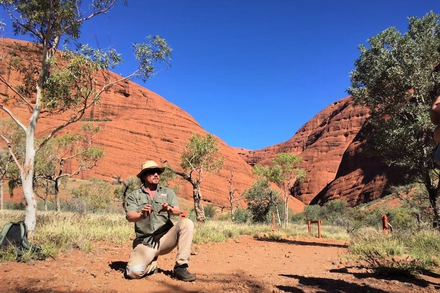 A man kneels down and gestures in front of a large red rock formation.