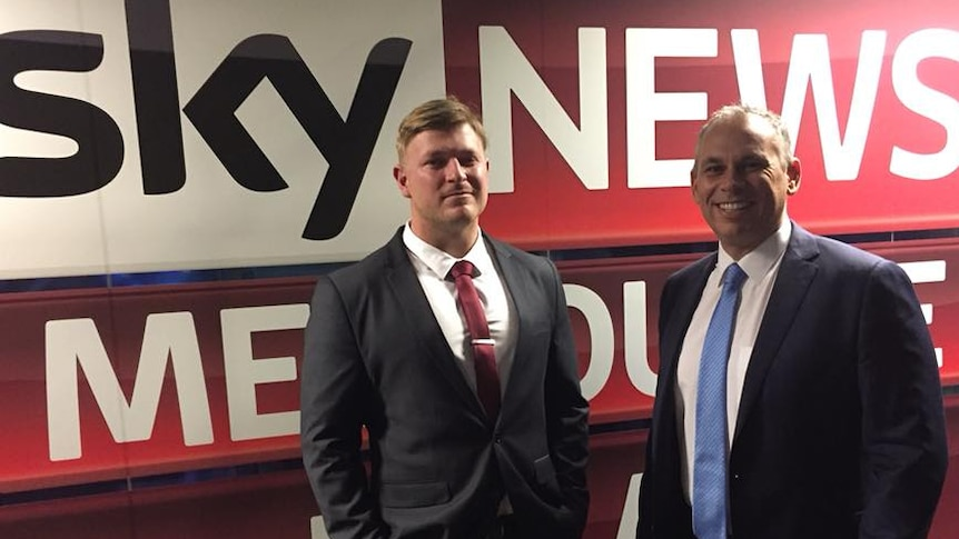Blair Cottrell and Adam Giles standing in front of a massive Sky News banner
