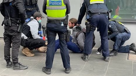 A man sitting on the ground in handcuffs surrounded by police.