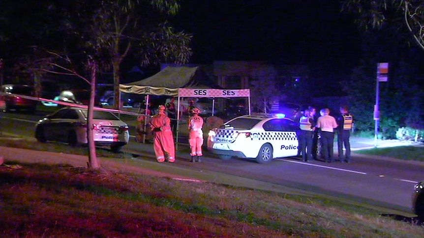 Several police and SES personnel stand near two police cars and an SES tent at night in a suburban street.