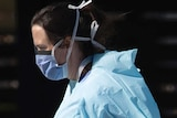 A hospital worker wearing blue scrubs and a face mask.