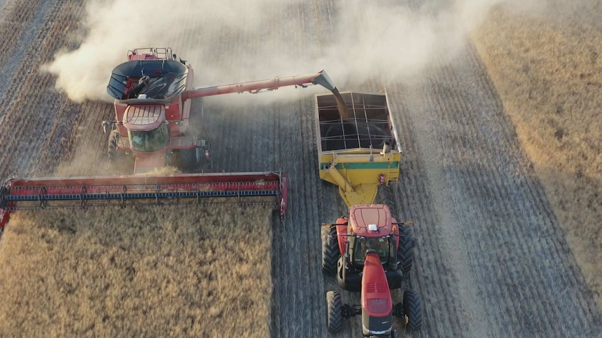 A drone shot capturing a harvest machine at work in a paddock.