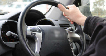 A hand on the steering wheel of a car