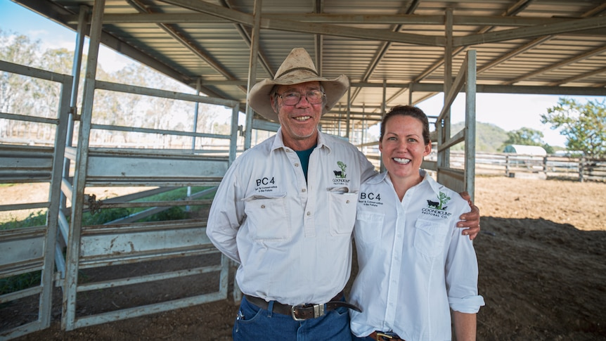 A man and a woman stand side by side in front of a cattle yard.