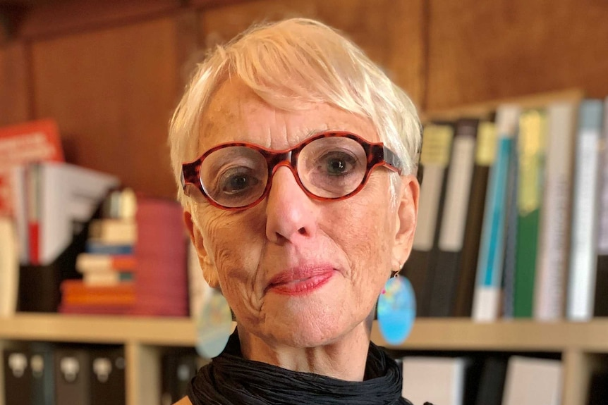 A portrait of lawyer Judy Courtin in a room lined with books.