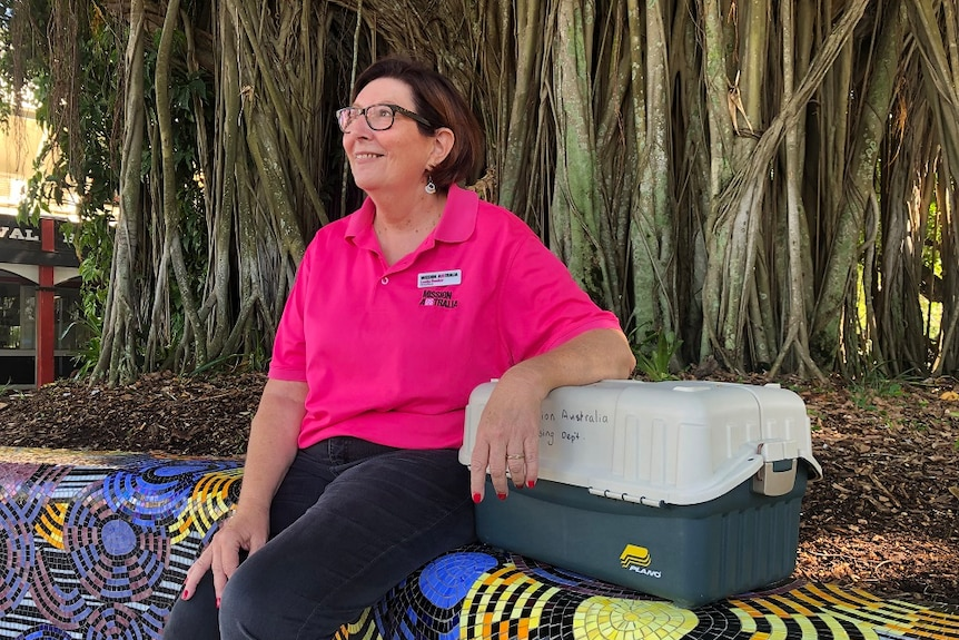 A woman in a pink 'Mission Australia' shirt leans on a first aid box while sitting under a large tree.