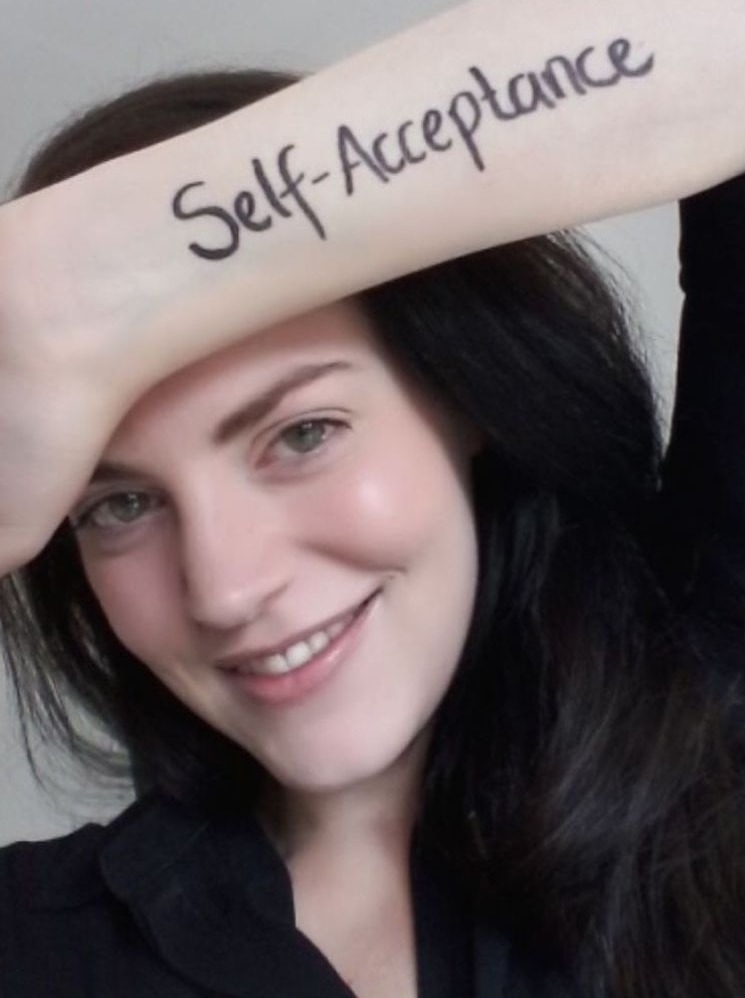 A woman smiling with 'self acceptance' written on her arm