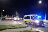 An ambulance with its lights on at night.