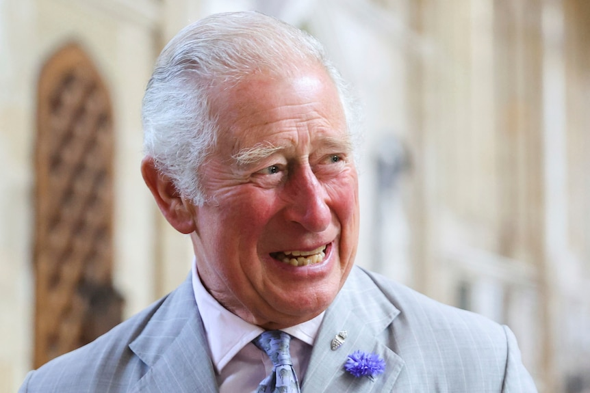 Prince Charles smiles wearing a pastel suit.