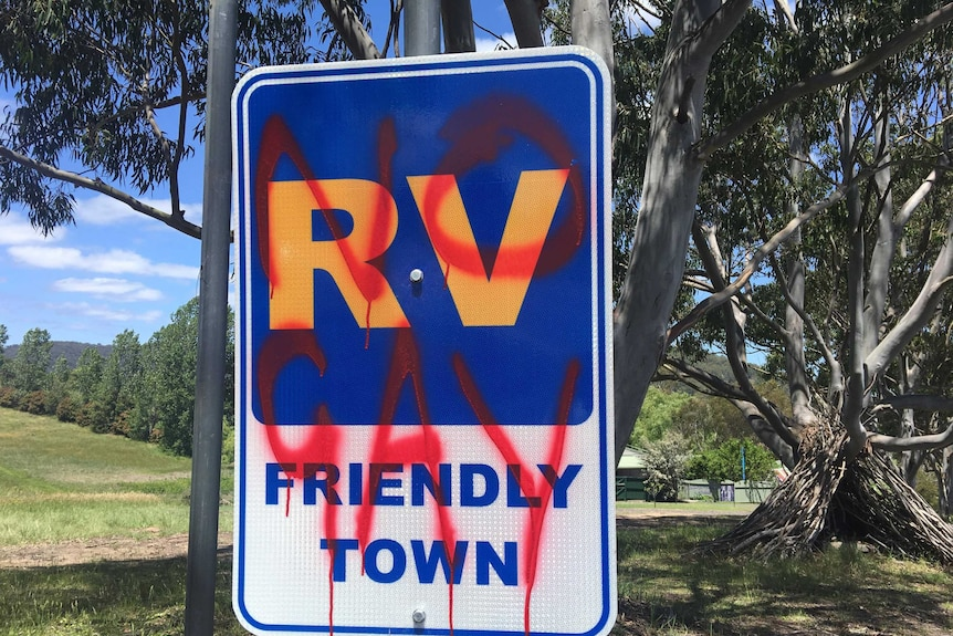 """""""No gay"""" spray painted in red over a street sign welcoming campervans to Cobargo"""