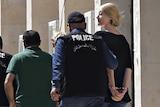 Police escort Tara Brown, in handcuffs, and Sally Faulkner to an awaiting car.