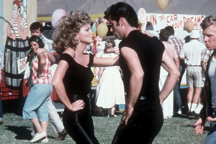 Olivia Newton-John and John Travolta dancing in a scene from Grease. Both are wearing black.