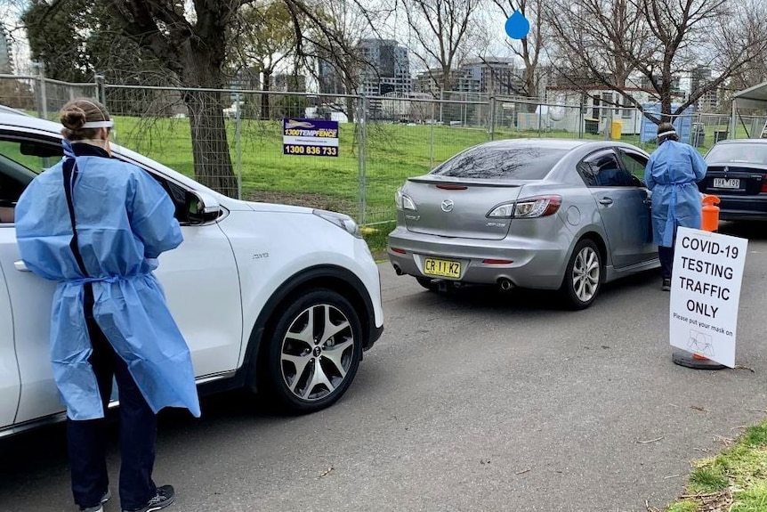 Health staff at cars in a queue near a COVID-19 testing sign.
