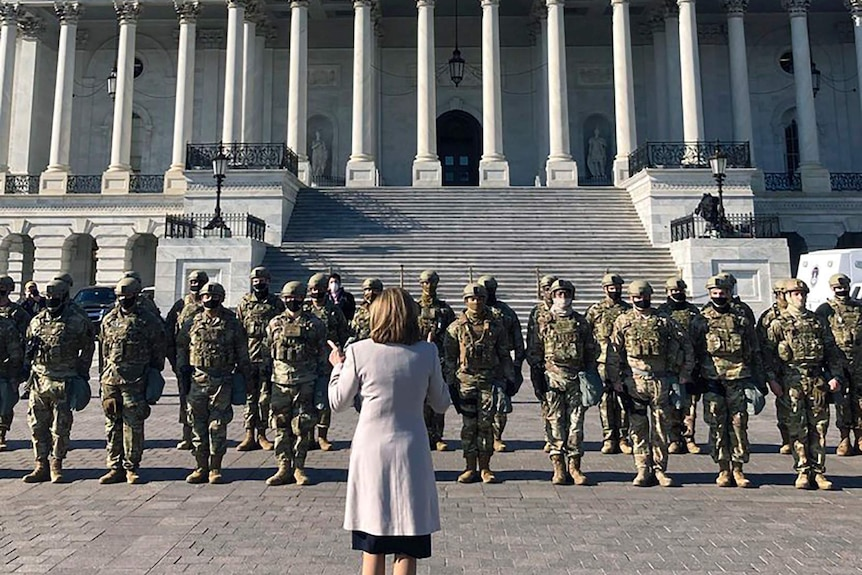 A woman wearing a grey coat stands in front of a group of men in uniforms and wearing helmets and masks in front of the Capitol.