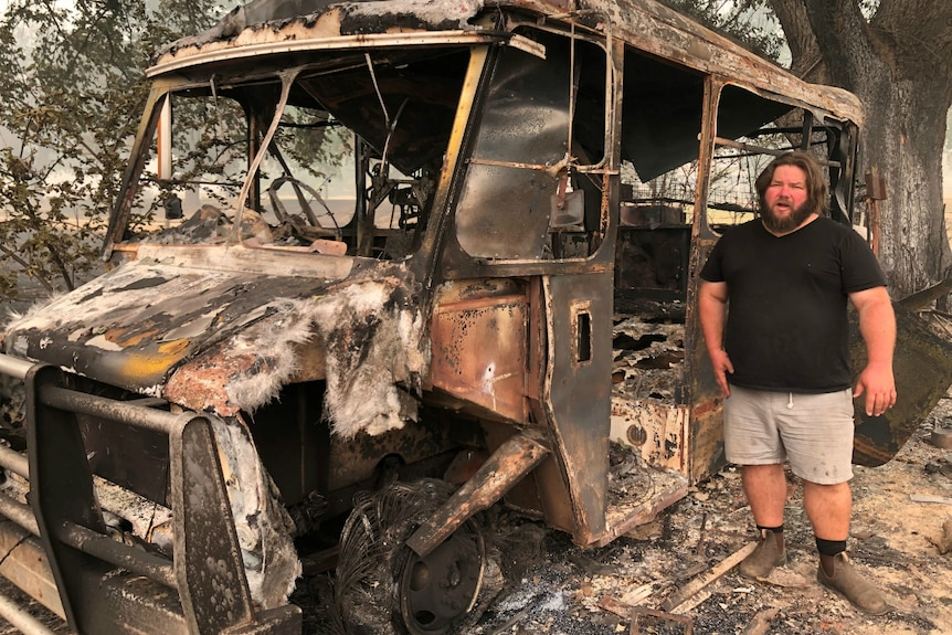 A man stands amid the rubble of a bushfire-hit property