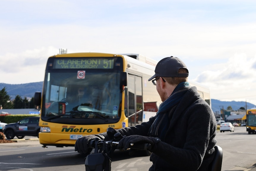 A man on a mobility scooter beside a suburban road, turning his body to look at a passing bus