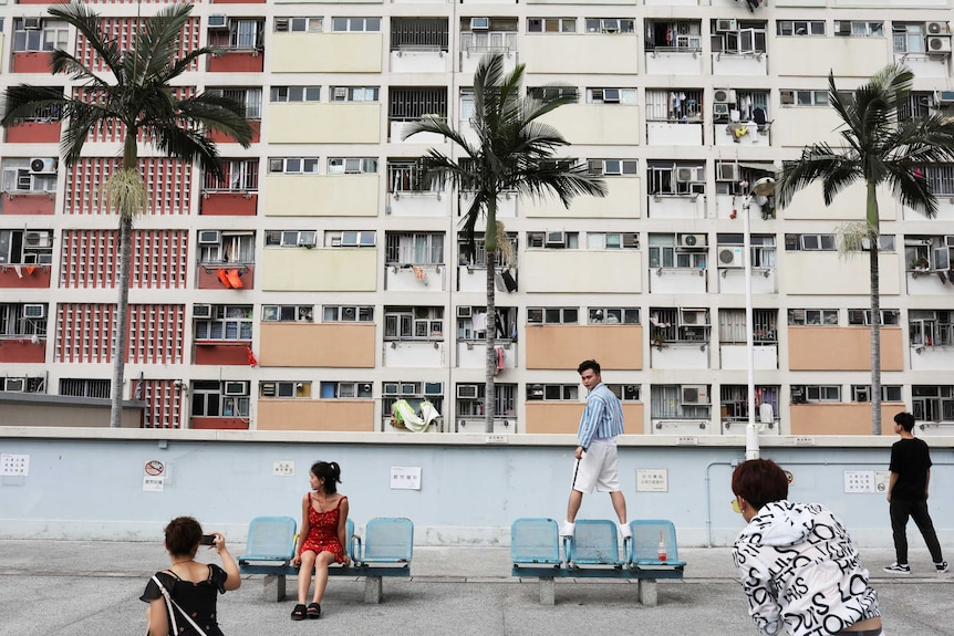 Hong Kong high rise apartments with people posing for pictures in front
