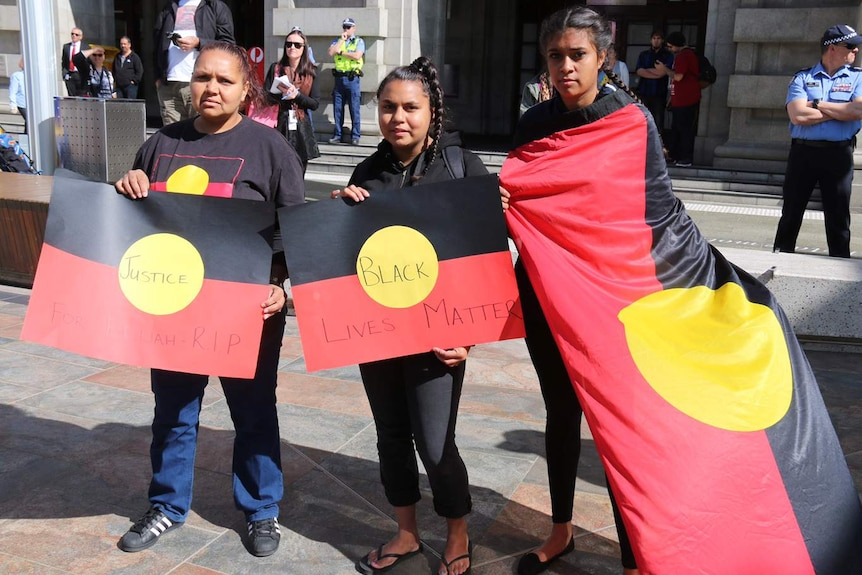 Three Aboriginal women stand holding Aboriginal flags with people and police officers in the background.